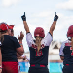 Softball players celebrate a victory