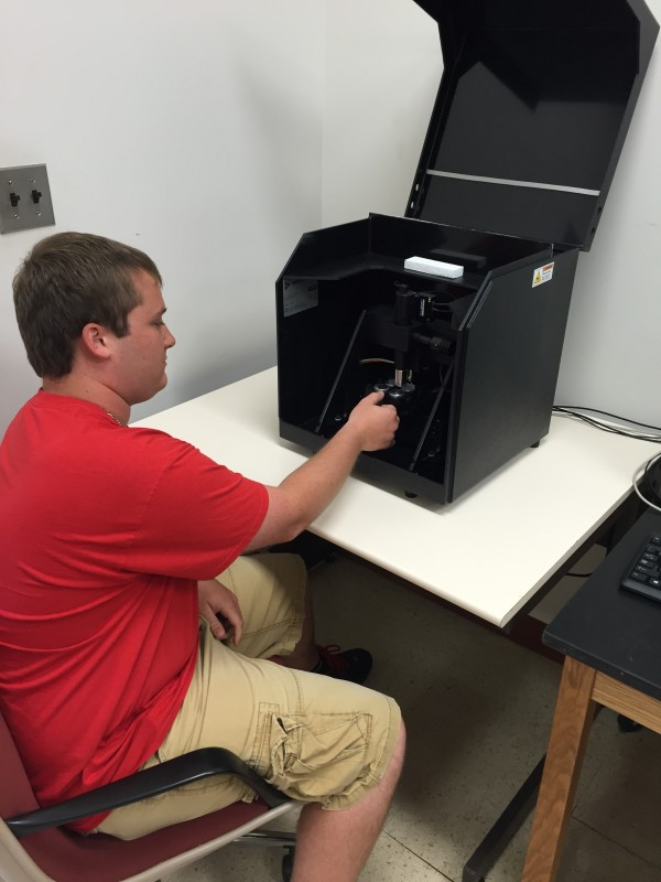 Dane Bower '16 inserts materials into a modular nanomechanical actuator for testing.