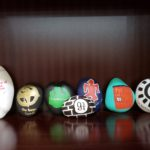 several rocks with book titles or images painted on them are lined up on a bookshelf.
