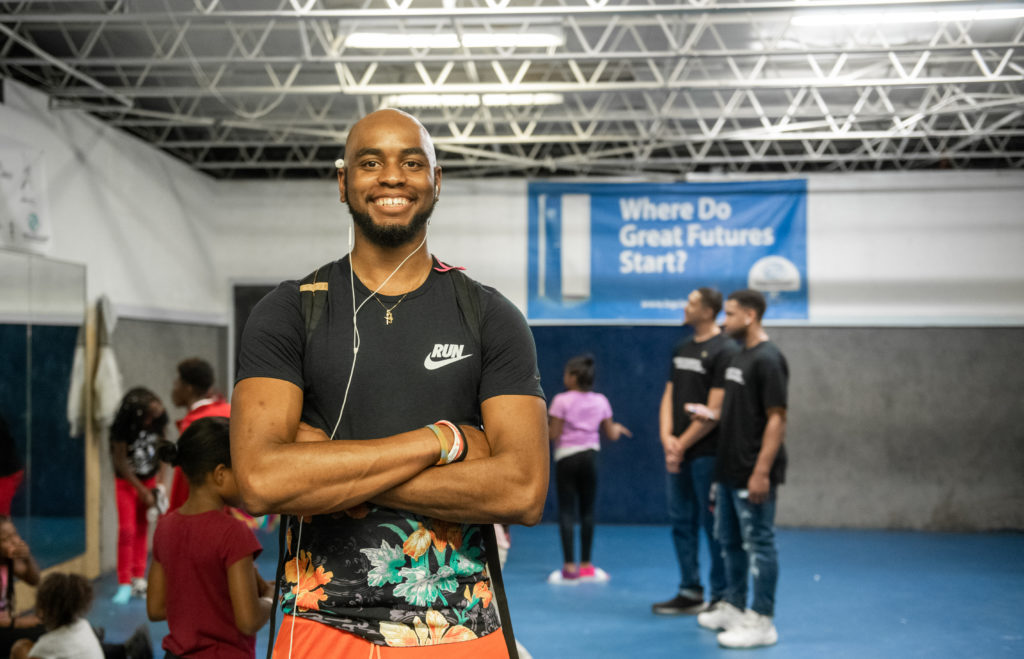 """Quinton Coe smiles at the Boys and Girls Club. In the background, people are visiting with each other and a sign reads, """"Where great futures start."""""""