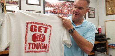 "Steve Koudelka holds a T shirt reading ""Get tough"""