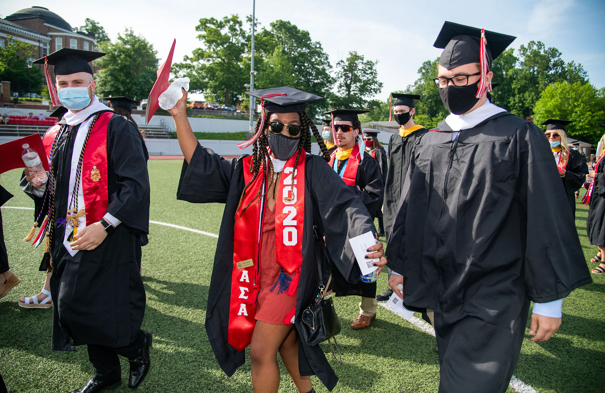 A student waves while walking into Commencement