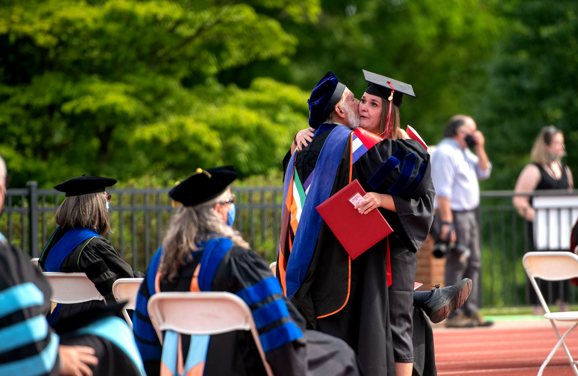 A student hugs a faculty member at Commencement
