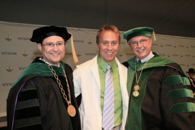Tim Wolff stands between two professors at his medical school graduation