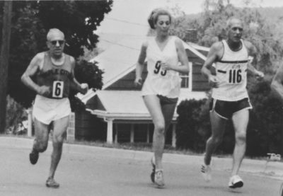 Three runners run down a street in a black and white photo