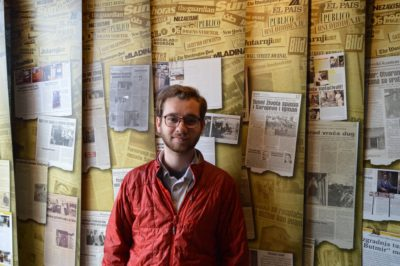 Student standing in front of a wall containing art depicting historic newspaper covers