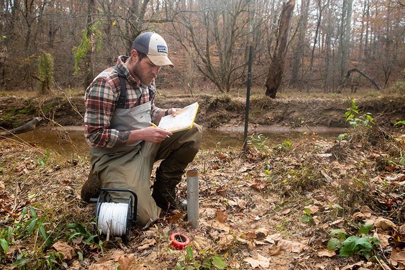 Ben Heskett samples water at College Lake in November 2020