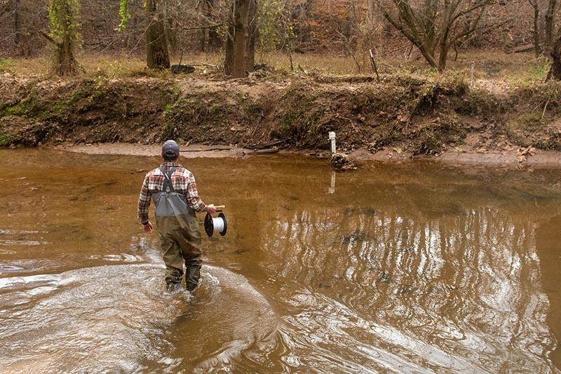 Ben Heskett wades through water in College Lake in November 2020