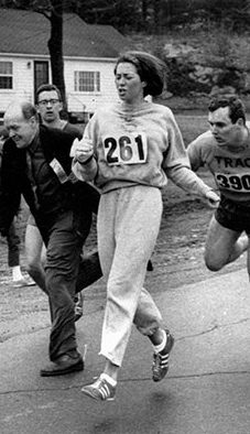 Black and white photo of Kathrine Switzer in 1972 Boston Marathon just after a race official was knocked away.