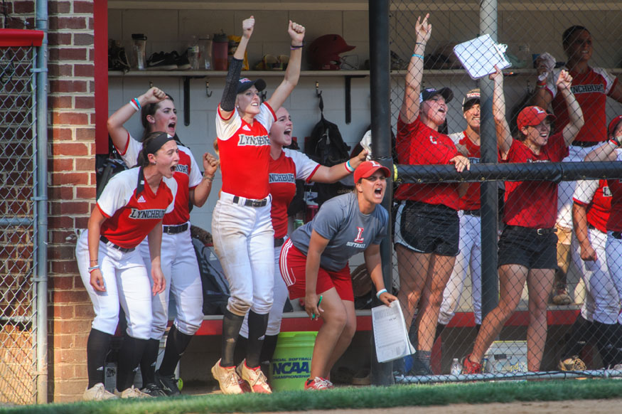 Softball players cheer during a game.