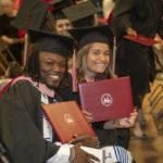 Two graduates display diploma portfolios with University of Lynchburg logos on them