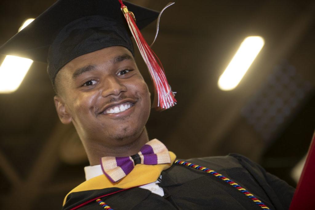 Graduate smiles at the camera