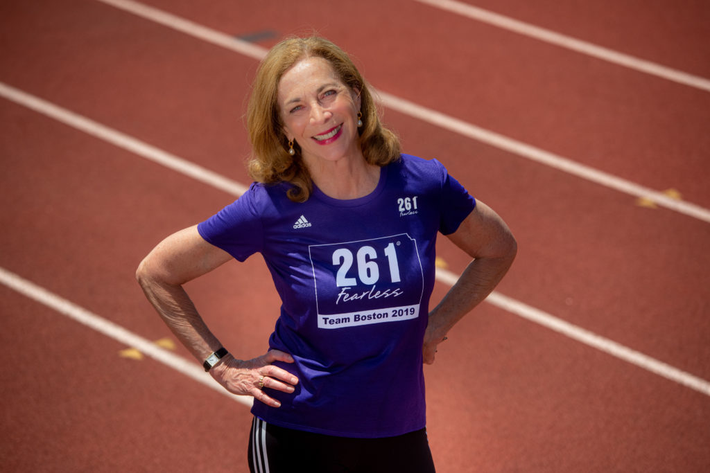 Kathrine Switzer standing on a track with a 261 Fearless shirt