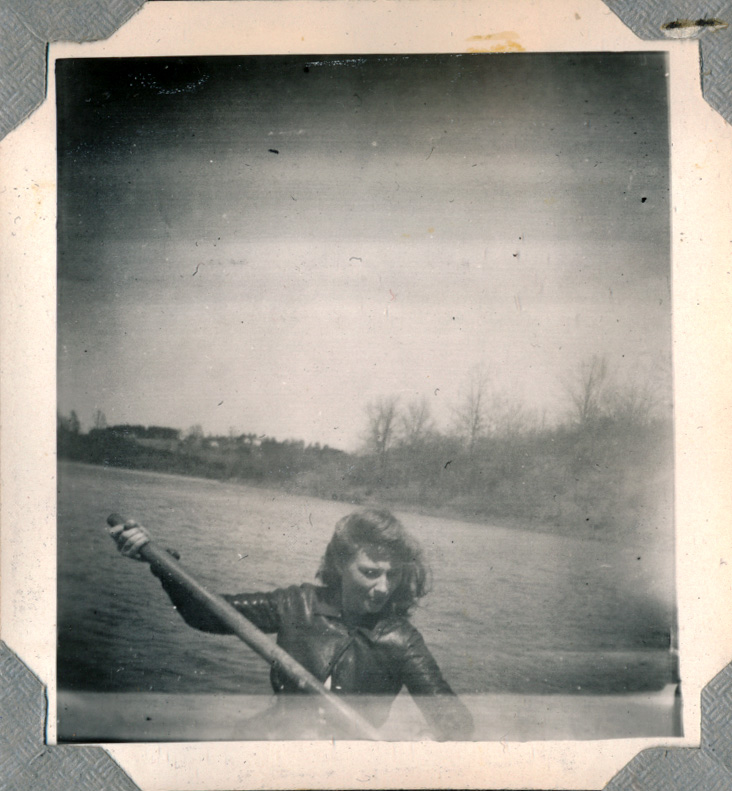 a woman paddles a boat in College Lake