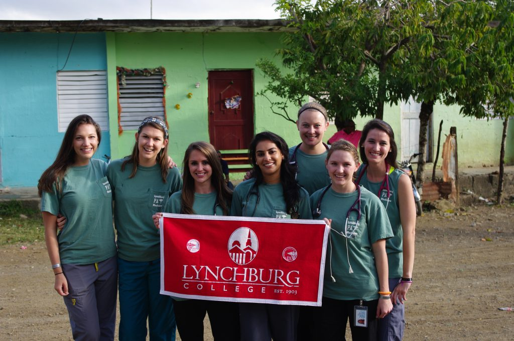 Seven students holding a sign that says Lynchburg College and shows the college seal