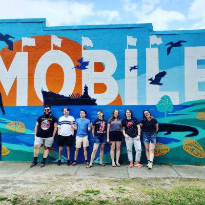 Students line up in front of a mural that spells Mobile.