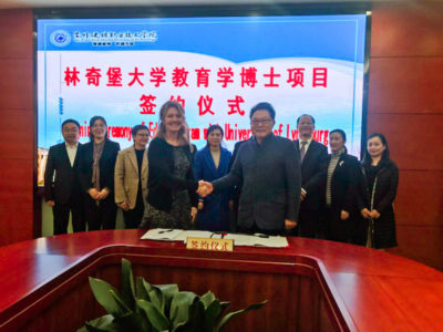 Sally Selden shakes hands with Ziaofeng Wei as others look on in the background. The agreement they signed for their schools sits on a table in front of them.