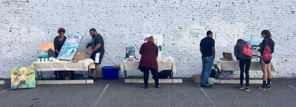 A photo of people working on art at three different tables with a white, brick wall in the background.