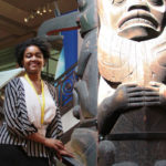 Ahsani Parker stands in front of a totem pole in the natural history museum
