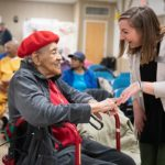 Katie Fabian talks with an elderly woman at the 50+ Health Fair in 2019
