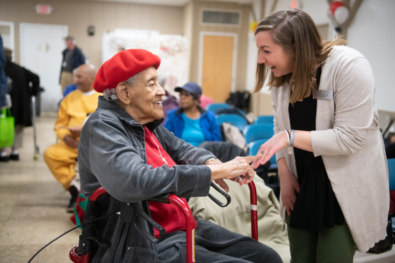 Kayla Hugate '20 at Health Fair with elderly woman laughing
