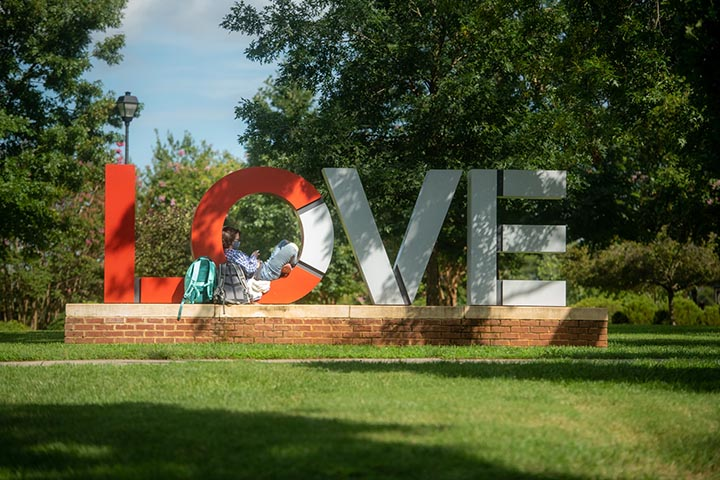 Sam Lipert sits in the LOVE sign on campus