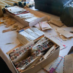 A pile of old, international letters on a white table