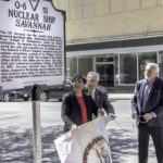 Treney Tweedy holds a large banner with the Virginia seal, which she has just removed from the historical marker.