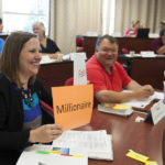 "A woman seated at a classroom table holds up an orange paper with the word ""Millionaire"" printed on it"