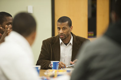Aaron Smith sits at a table and speaks to students