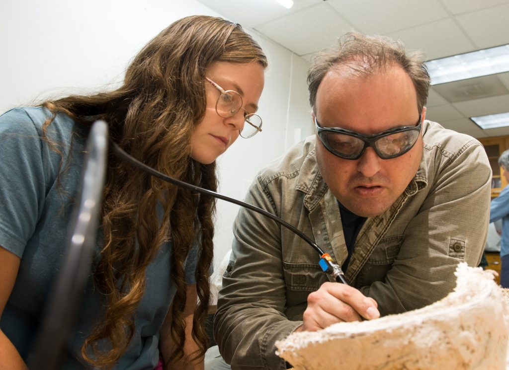 Photo of two scientists examining a fossil as one holds an air chisel.