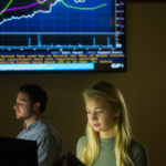 Rebecca Taylor works at a computer in a trading room with a stock market graph on a screen in the background.