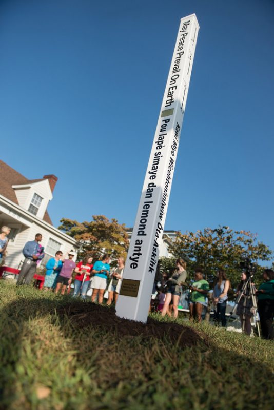 """A photo of the peace pole in front of the Spiritual Life Center. The pole is tall and white with the message """"May Peace Prevail on Earth"""" written in eight languages. It also includes a plaque with the message written in Braille."""