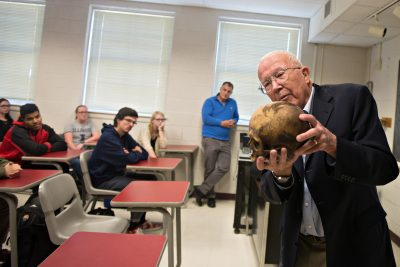 Photo of Dr. William Bass showing a skull to students in a criminology class.