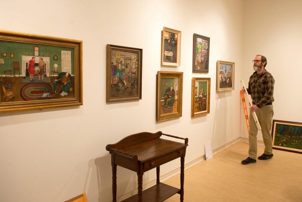 Steve Riffee hangs Queena Stovall paintings in the Daura Gallery.