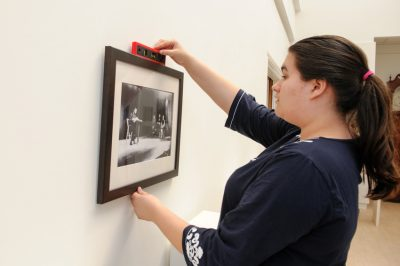 Shelby Miller hangs a painting in the Daura Gallery