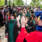 Graduates high-fiving faculty at Commencement