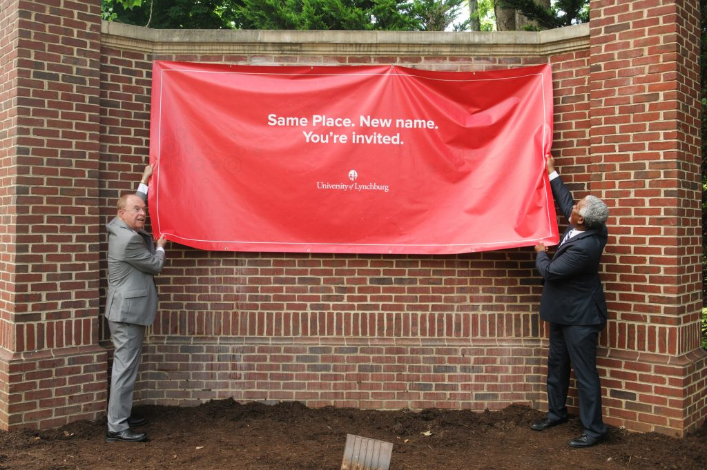 President Garren and Nat Marshall prepare to remove a red banner over the new sign