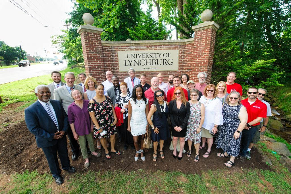 faculty gather in front of new University of Lynchburg sign