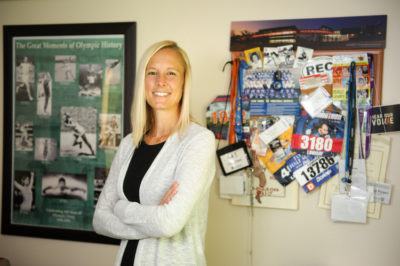 Lindsay Pieper poses in front of sports memorobilia hanging on a wall