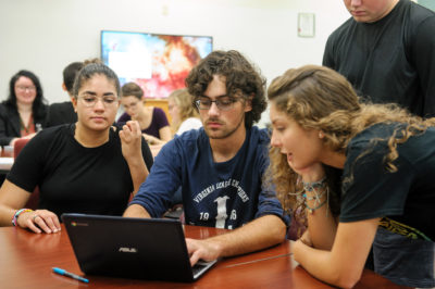 Students gather around a laptop where one of them types