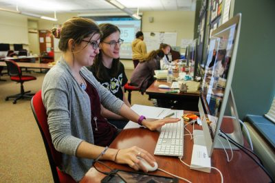 Two students work together at a graphic design computer