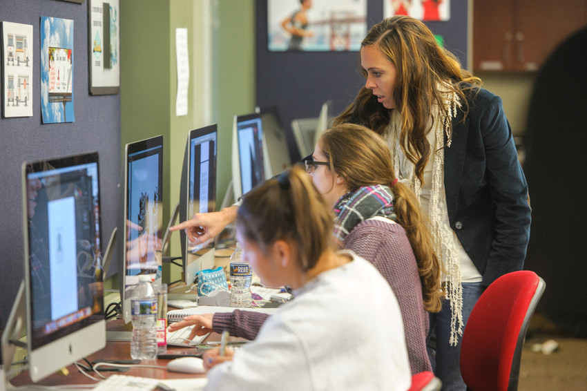 Students work on graphic design projects as professor Ursula Bryant points at one of the computer screens
