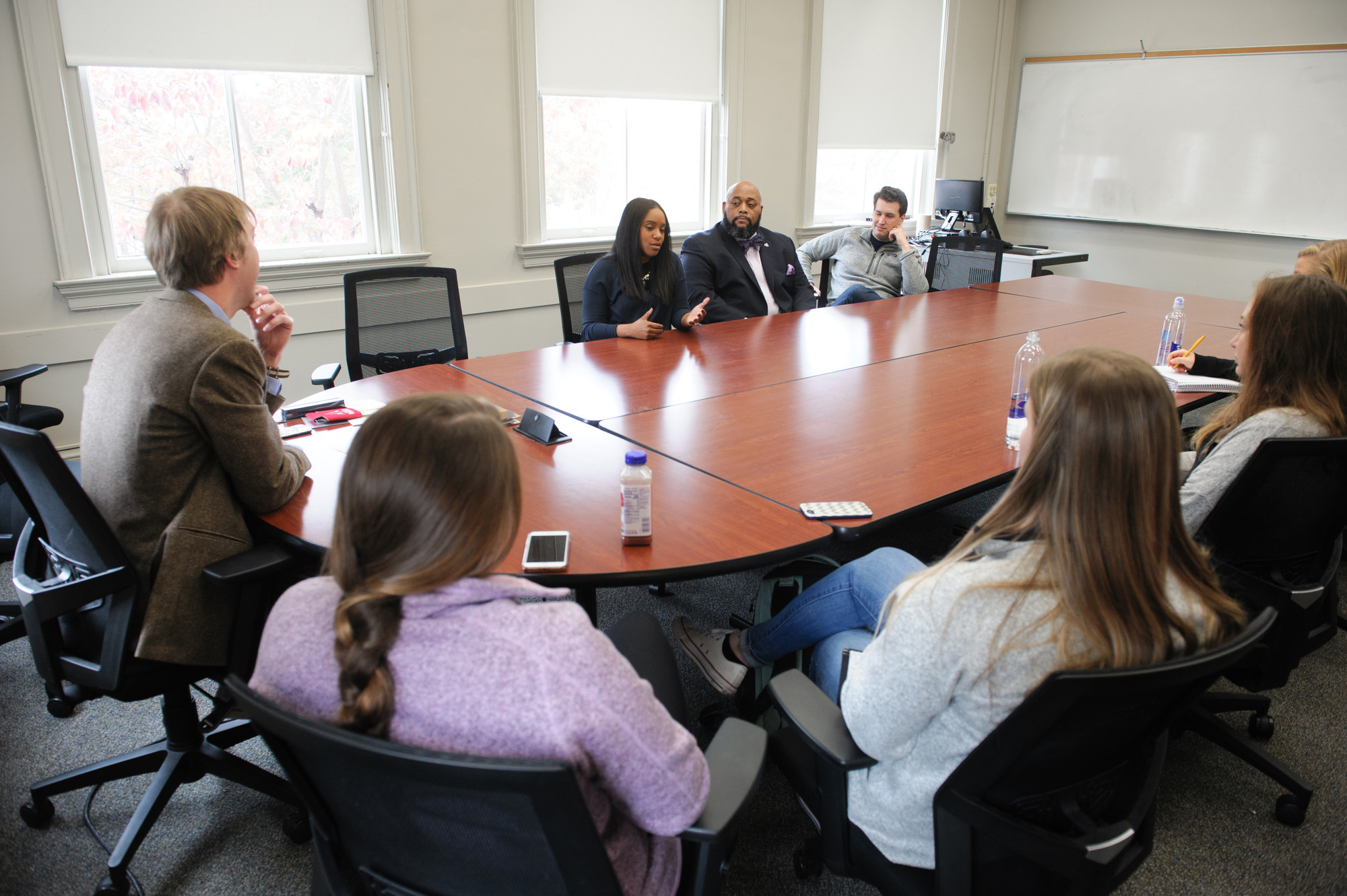 students and guest speakers gathered around a classroom table