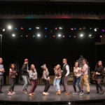 Curtain call students on stage dancing with cardboard coffee cups as props