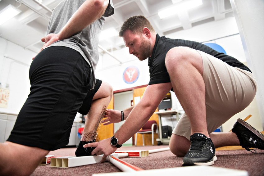 C.J. Rosenborough guides an athlete's ankle and leg in a procedure that measures range of motion