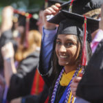 A graduate smiles during commencement while others around her turn their tassels