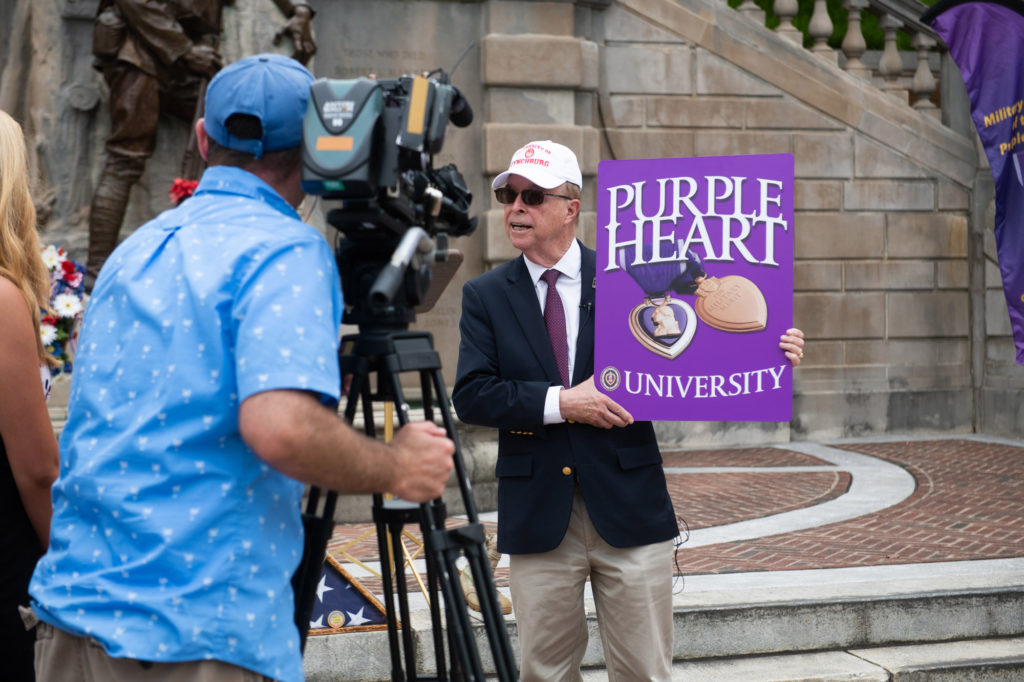 "President Garren holding a large purple sign with the words ""Purple Heart University"" as he talks to reporters"