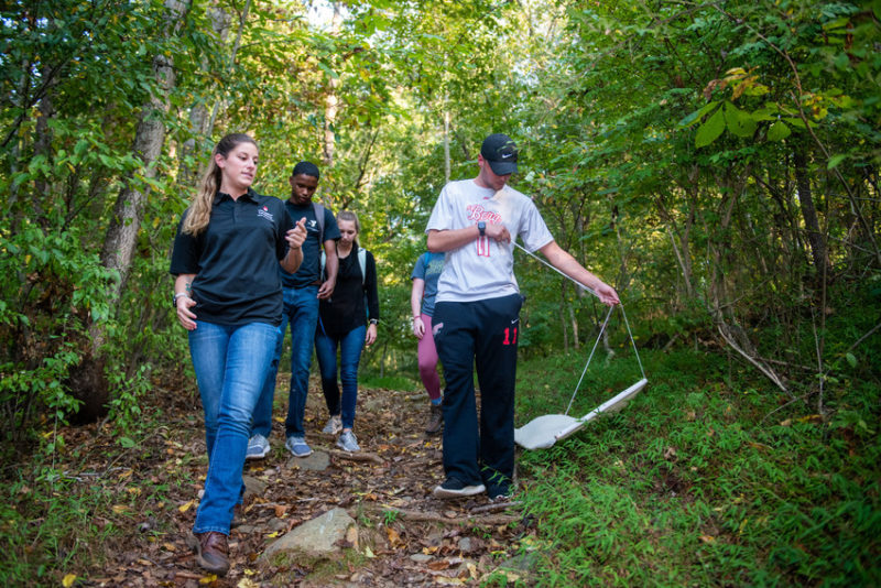 Students walk down a trail dragging a white cloth on the grount