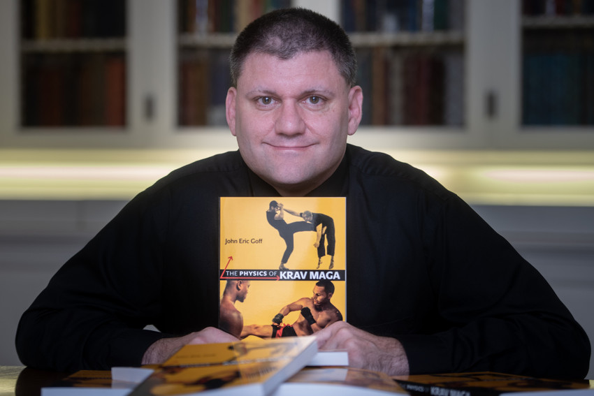 """Eric Goff holding a copy of his book """"The Physics of Krav Maga"""""""